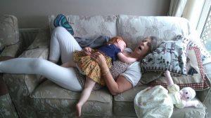 Some people sleeping on a sofa